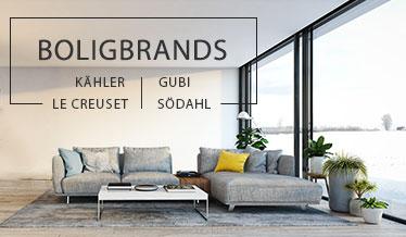 Grå sofa med gule og blå puder i en skandinavisk indretning