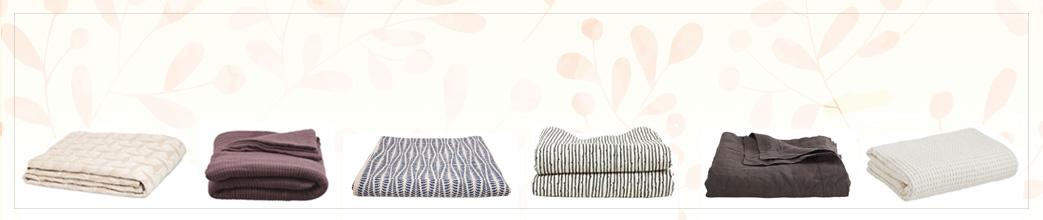 Sengetæpper i varme farver og diskrete mønstre