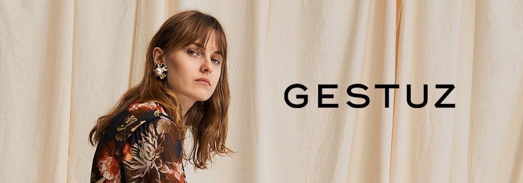 Pige og Gestuz logo på beige baggrund