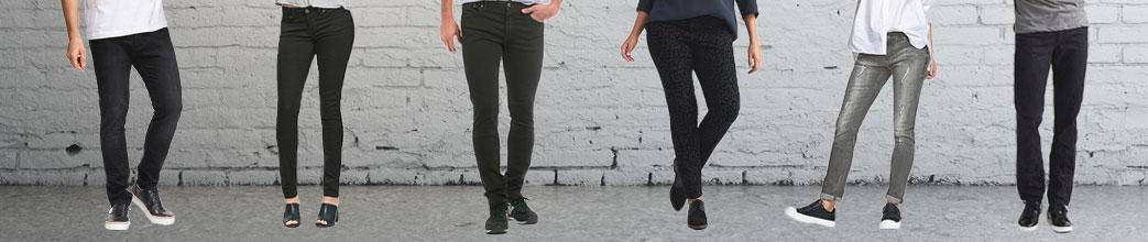 Modeller med sorte jeans foran en grå mur